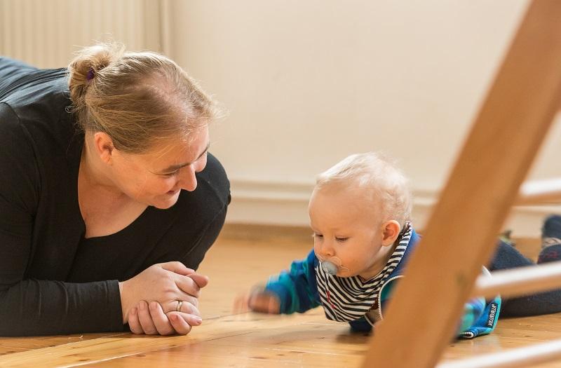 Daniela Scheurer im Kontakt mit einem Baby, das auf dem Bauch liegt