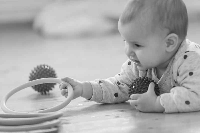 Baby in Bauchlage ergreift einen Ring
