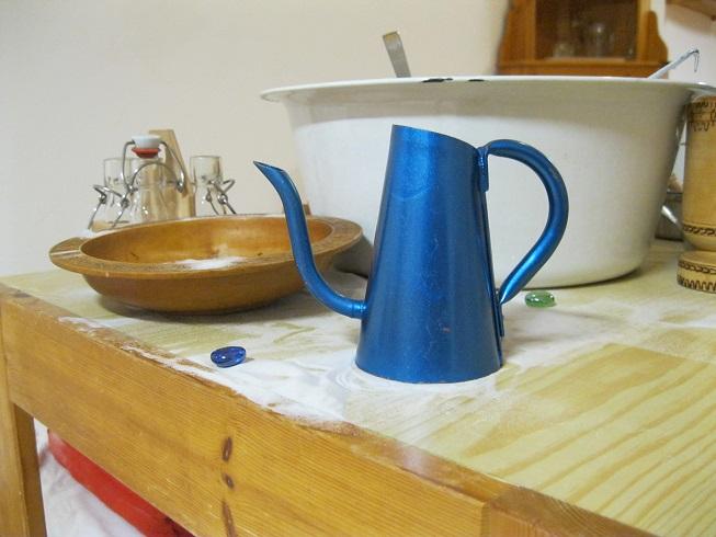 blaue Kanne und Holzteller auf einem Tisch mit weißem Sand