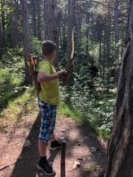 Bub mit Bogen im Wald